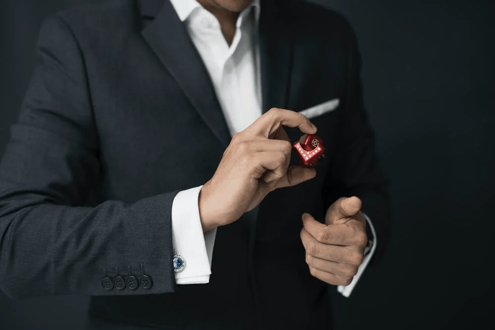 A luxurious businessman in a suit holding a red cube
