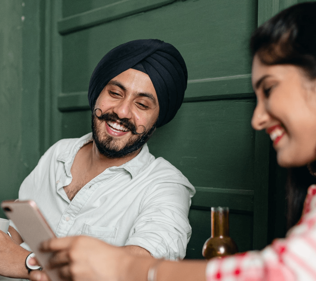 An Indian couple laughing and enjoy CallApp together