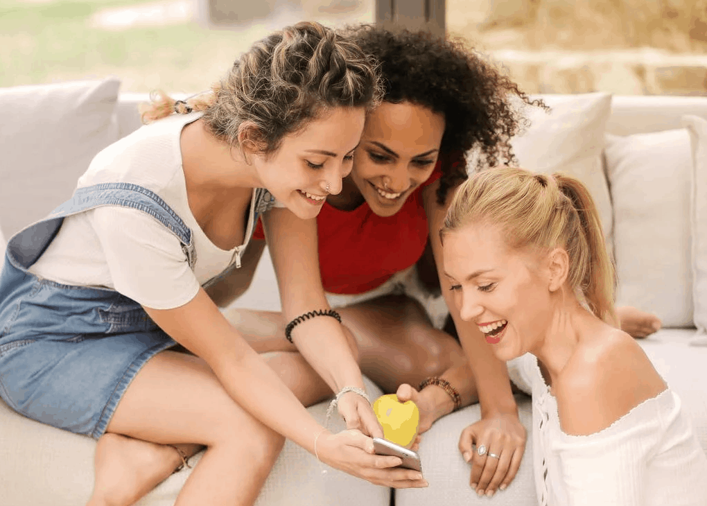 Three girls smiling and laughing as they hold the phone