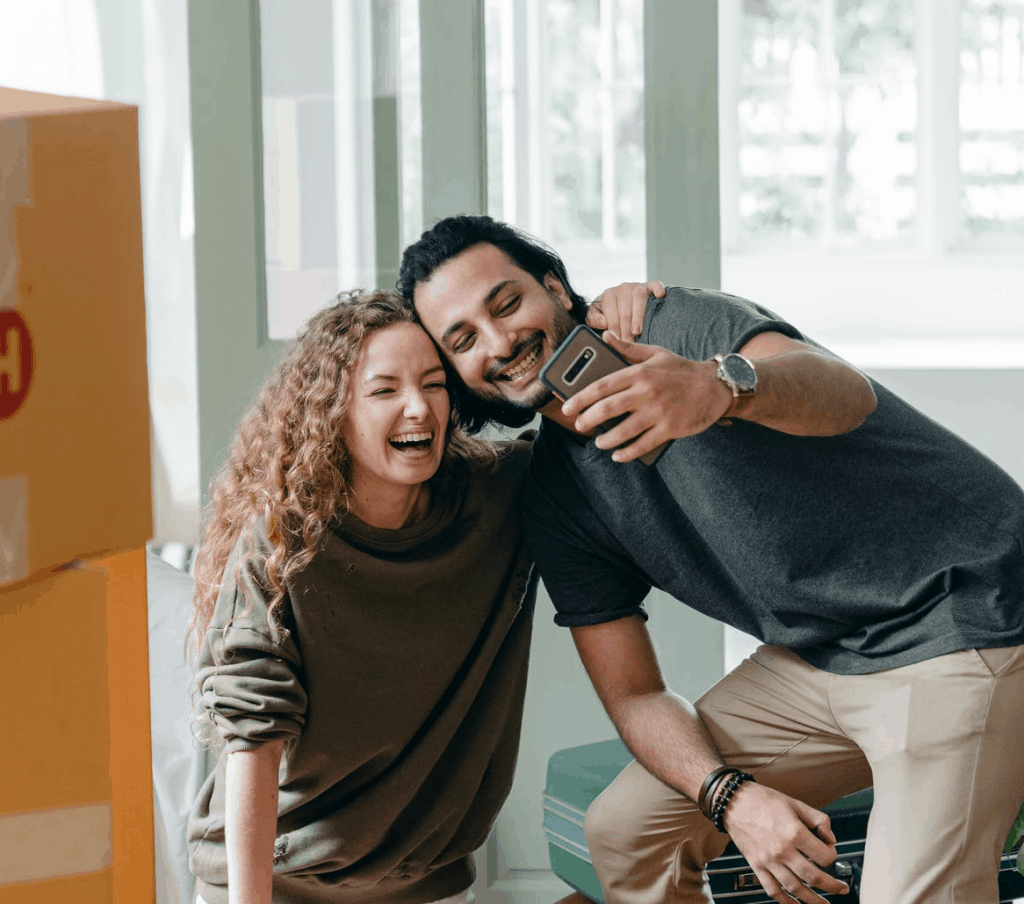 A couple holding a phone together smiling at it