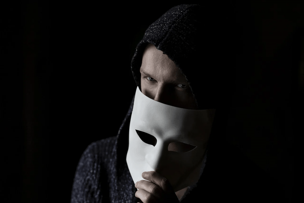 A young man holding a white mask below his eyes