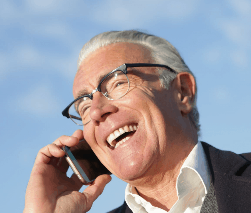 An elderly man smiling as he speaks on the phone outside