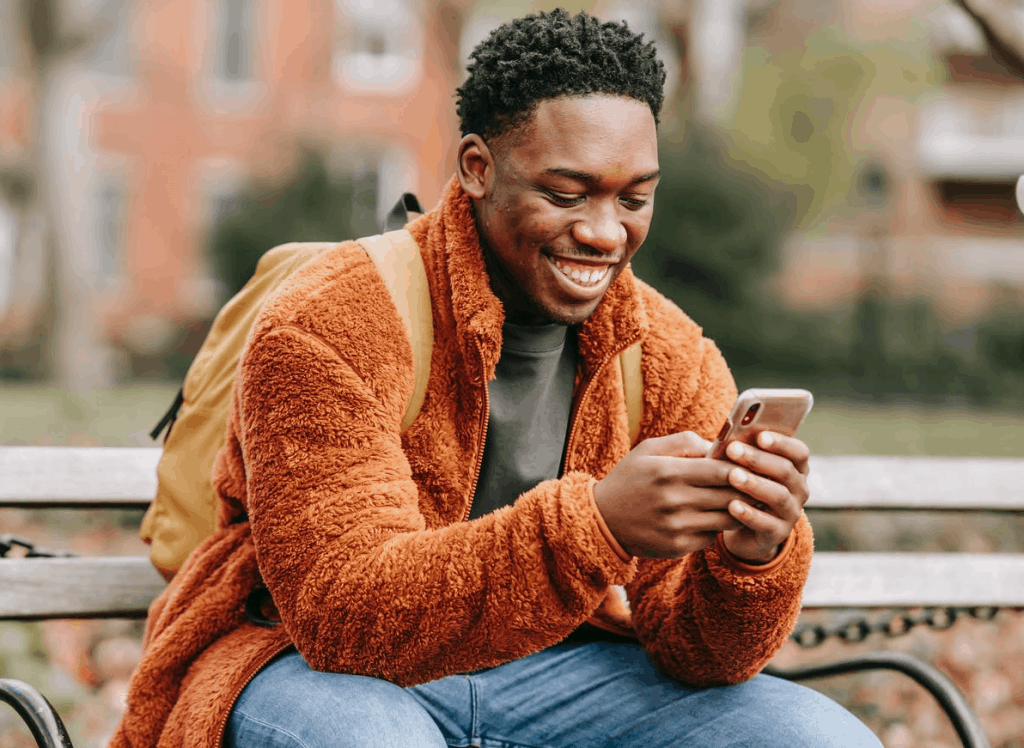 An African American man holding his phone and smiling on a bench