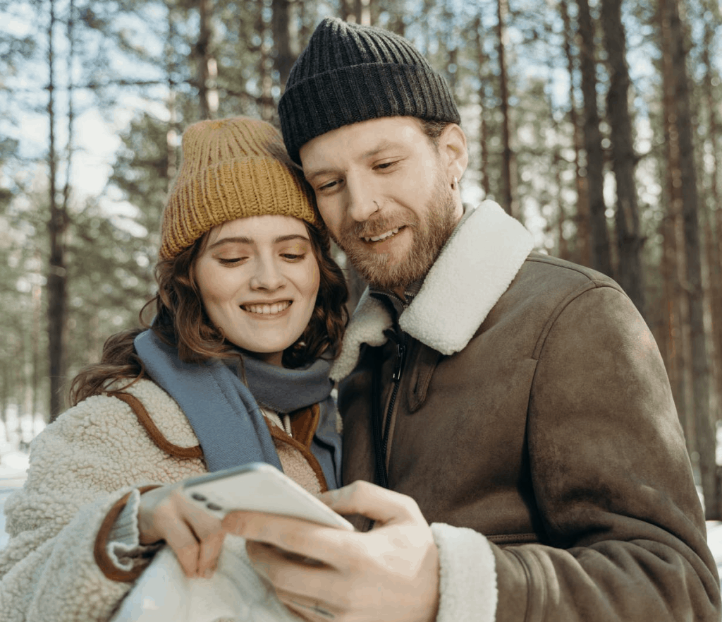 A couple smiling at a phone together in the winter cold