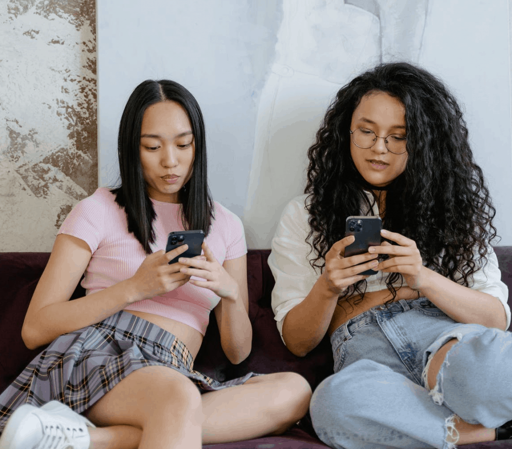 Two girls holding their phones