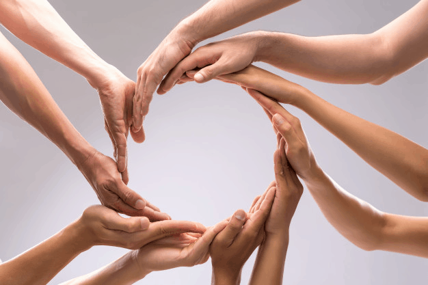 A group of people holding their hands together